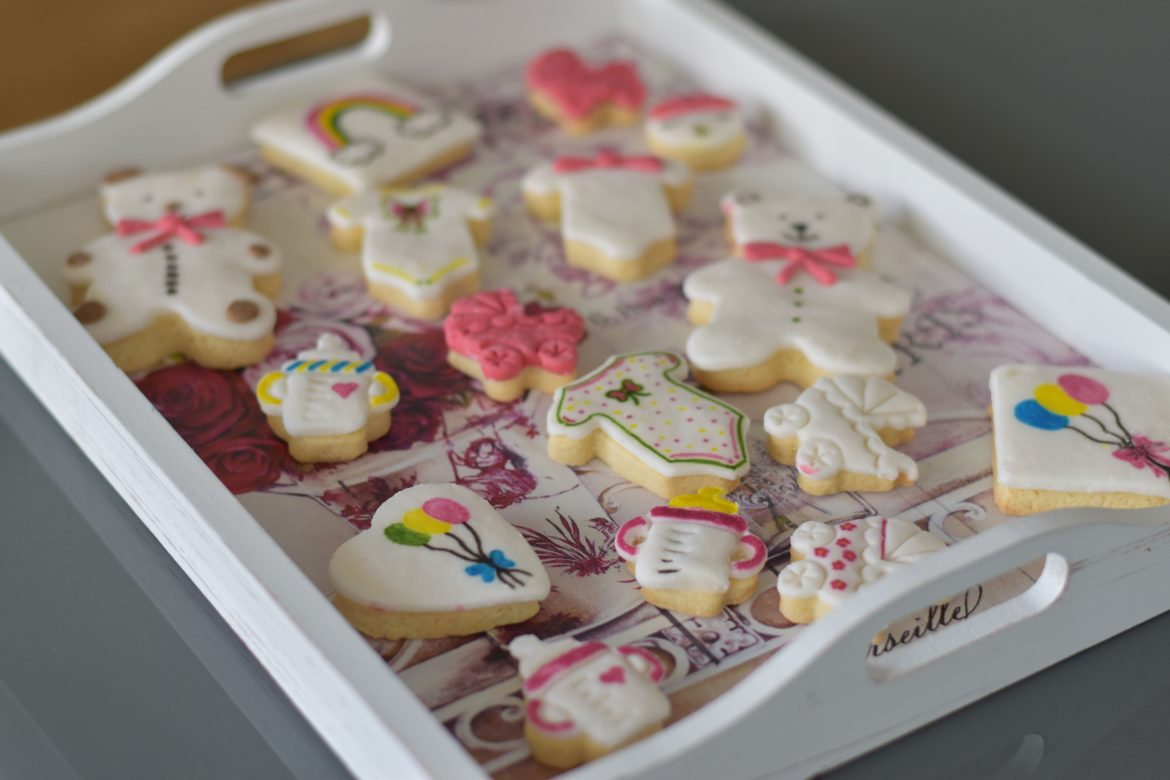 Baby shower decorated cookies with fondant icing in a vintage tray